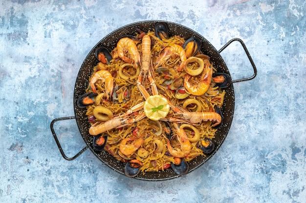 Bovenaanzicht van een pan met smakelijke zeevruchten en pastagerecht
