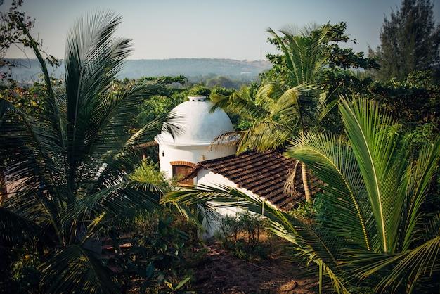 Bovenaanzicht van een pannendak en een witte stenen toren in het midden van een regenwoud. een gebouw in een palmentuin, een afgezonderde woning
