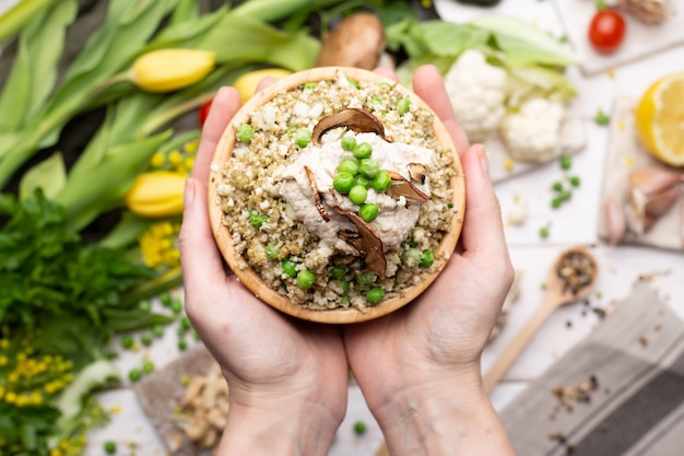 Bovenaanzicht van een persoon die een kom heerlijke veganistische salade vasthoudt