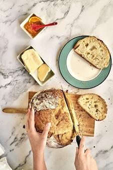 Bovenaanzicht van een persoon die een vers gebakken brood op een houten bord met boter en marmelade snijdt