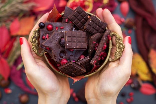 Bovenaanzicht van een persoon met kleine heerlijke veganistische chocoladerepen met bessen