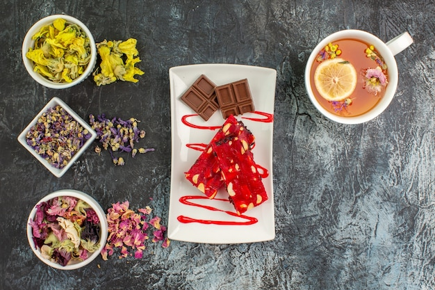 Bovenaanzicht van een plaat van chocolade met een kopje kruidenthee en kommen met droge bloemen op grijze grond