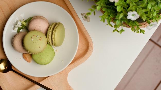 Bovenaanzicht van een plaat van franse kleurrijke macarons op salontafel versierd met plantpot