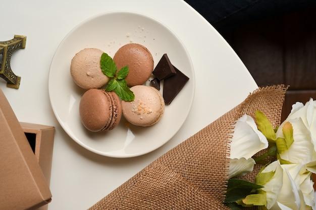 Bovenaanzicht van een plaat van franse kleurrijke macarons op tafel met doos en bloemenbrunch in de woonkamer