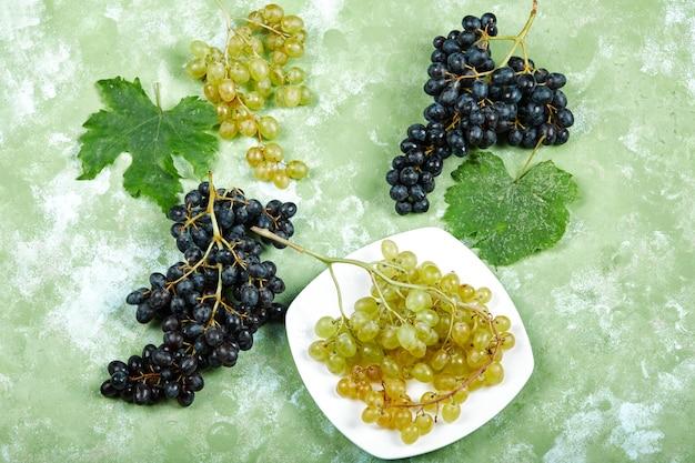Bovenaanzicht van een plaat van witte druiven en zwarte druiven met bladeren op groen oppervlak