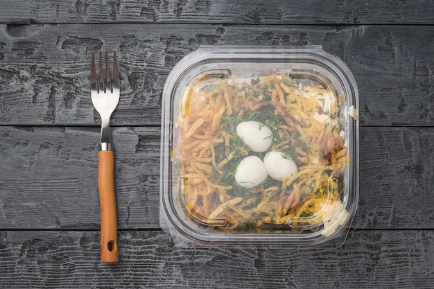 Bovenaanzicht van een plastic bak met een salade in de vorm van een nest