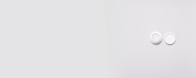Bovenaanzicht van een plastic pot met cosmetische op een grijze achtergrond met kopie-ruimte. minimale compositie