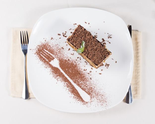 Bovenaanzicht van een portie versgebakken cake gegarneerd met geraspte chocolade en versierd met de omtrek van een vork in chocoladepoeder