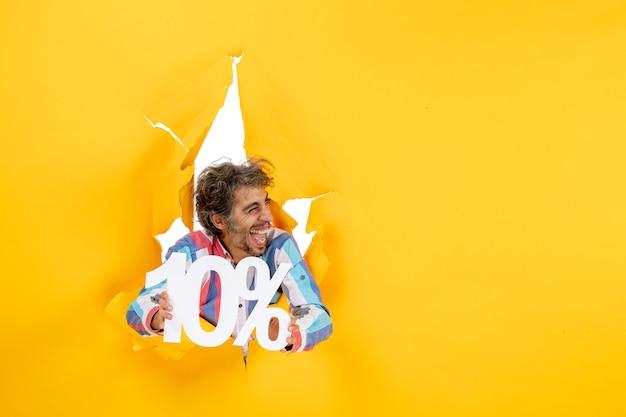 Bovenaanzicht van een positieve bebaarde man met tien procent in een gescheurd gat in geel papier