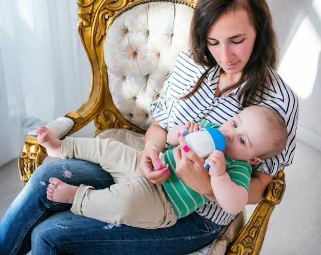 Bovenaanzicht van een positieve jonge moeder die haar zoontje in haar armen houdt terwijl ze op een mooie gezellige stoel in de woonkamer zit