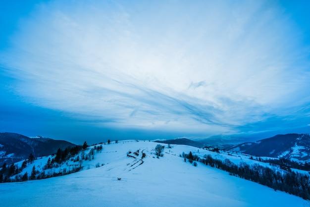 Bovenaanzicht van een prachtig betoverend landschap van besneeuwde bergen en heuvels met bomen en mist