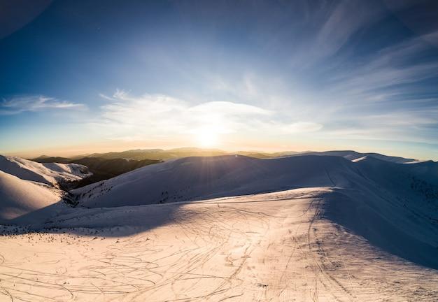 Bovenaanzicht van een prachtig betoverend uitzicht op de skipiste met ski-pistes gelegen in de bergen op een zonnige winterse ijzige avond