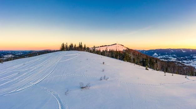 Bovenaanzicht van een prachtig betoverend uitzicht op de skipiste met skipistes gelegen in de bergen op een zonnige ijzige winteravond. vakantie en toerisme concept in de winter. copyspace