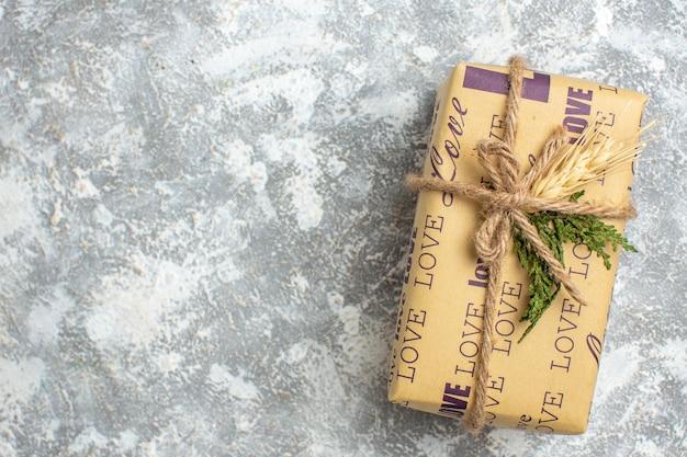 Bovenaanzicht van een prachtig kerstcadeau met liefdesinscriptie aan de linkerkant op ijsoppervlak