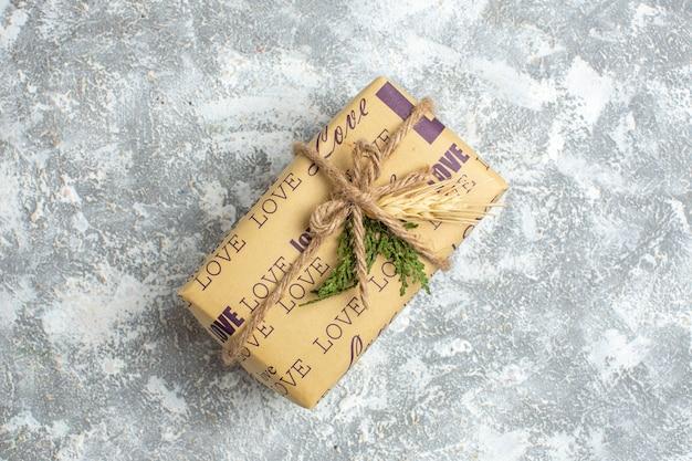 Bovenaanzicht van een prachtig kerstcadeau met liefdesinscriptie op ijstafel