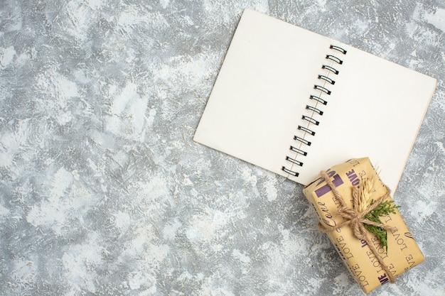 Bovenaanzicht van een prachtig kerstcadeau met liefdesinscriptie op open notitieboekje aan de linkerkant op ijstafel