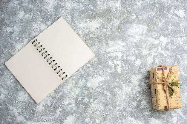 Bovenaanzicht van een prachtig kerstcadeau met liefdesinscriptie op open notitieboekje op ijstafel
