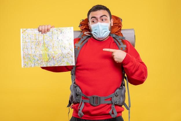 Bovenaanzicht van een reiziger die een medisch masker draagt met een rugzak die op een gele achtergrond wijst