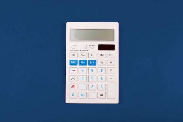 Bovenaanzicht van een rekenmachine op een klassiek blauw