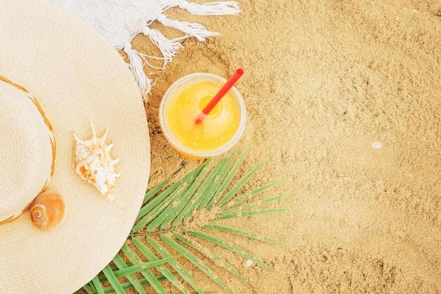 Bovenaanzicht van een rieten hoed, schelpen, een palmtak en vers geperst sinaasappelsap in een plastic beker op het zand. strand plat lag met kopie ruimte.