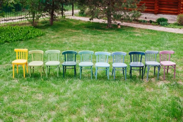 Bovenaanzicht van een rij houten weense stoelen geschilderd in vrolijke felle kleuren in de achtertuin