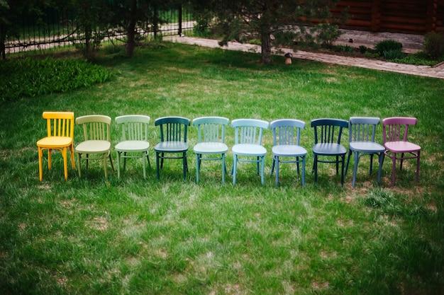 Bovenaanzicht van een rij kleurrijke regenboogkleurige stoelen die in een rij staan op het gazon in de achtertuin v...