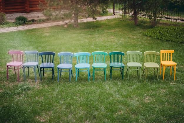 Bovenaanzicht van een rij kleurrijke weense stoelen op een rij een kinderverjaardagsfeestje in de tuin op de...