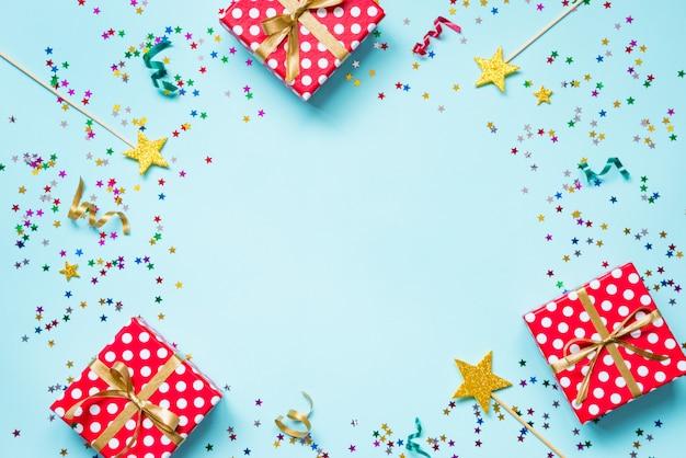 Bovenaanzicht van een rode gestippelde geschenkdozen, gouden toverstokjes, kleurrijke confetti en linten op blauwe achtergrond. viering concept. kopieer ruimte.