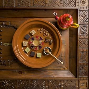 Bovenaanzicht van een ronde houten plaat met verschillende soorten vierkante snoepjes en noten