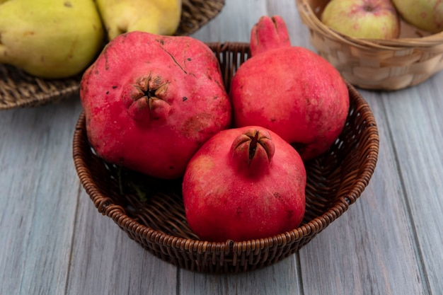 Bovenaanzicht van een ronde vrucht met een rode leerachtige korst granaatappels op een emmer met appels en kweeperen op een grijze achtergrond