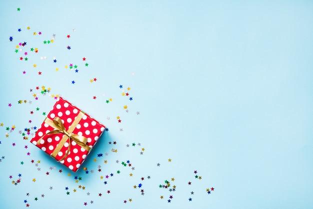Bovenaanzicht van een rood gestippelde geschenkdoos en verspreide glinsterende stervormige confetti op blauwe achtergrond. viering concept. kopieer ruimte.