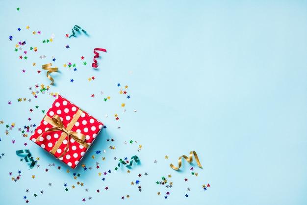 Bovenaanzicht van een rood gestippelde geschenkdoos, verspreide glinsterende stervormige confetti en kleurrijke linten op blauwe achtergrond. viering concept. kopieer ruimte.