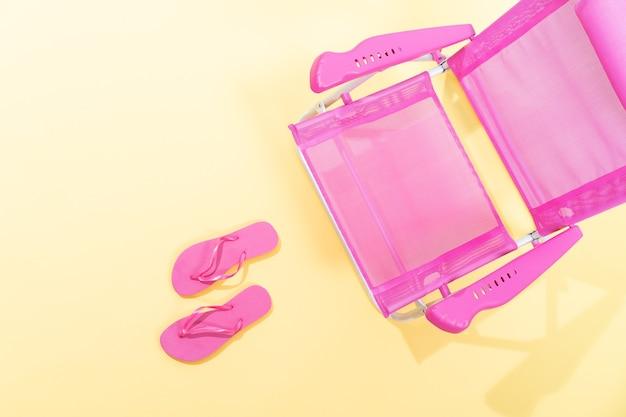 Bovenaanzicht van een roze strandstoel met roze slippers