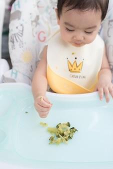 Bovenaanzicht van een schattig aziatisch babymeisje met een babyschort zittend op de eettafel en eet zelf broccoli, baby led weaning concept