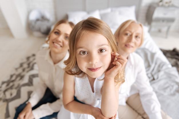 Bovenaanzicht van een schattig bruinogig meisje dat haar haar met één hand aanraakt, het op de andere laat rusten terwijl haar moeder en grootmoeder op de achtergrond zitten en glimlachen
