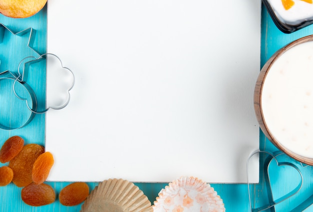 Bovenaanzicht van een schetsboek en gedroogde abrikozen kwark yoghurt en cookie cutters gerangschikt op blauw