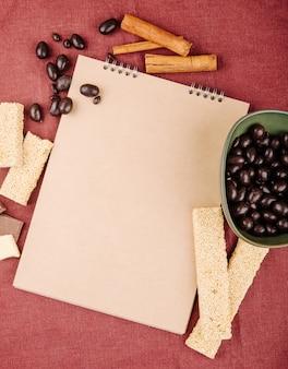 Bovenaanzicht van een schetsboek en geglazuurde chocoladesnoepjes in een kom met stukjes sesamkozinaki op donkerroze tafelkleed