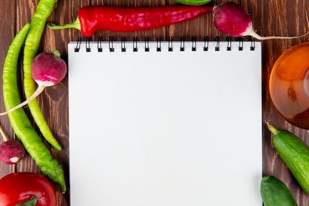 Bovenaanzicht van een schetsboek en groenten chili pepers radijs en komkommers op rustiek hout