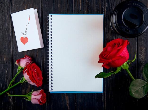 Bovenaanzicht van een schetsboek en rode rozen met een briefkaart en een papieren kopje koffie op donkere houten achtergrond