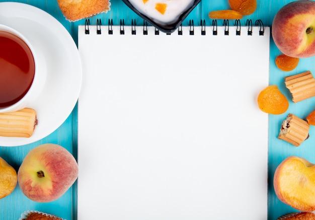 Bovenaanzicht van een schetsboek en verse perziken met muffins, gedroogde abrikozenkoekjes en een kopje thee gerangschikt op blauw