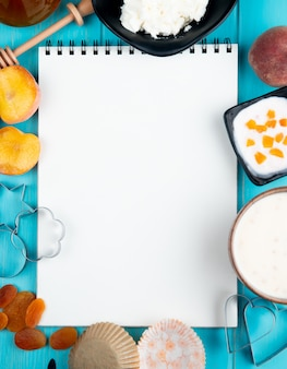 Bovenaanzicht van een schetsboek en verse rijpe perziken gedroogde abrikozen kwark yoghurt en cookie cutters gerangschikt op blauw