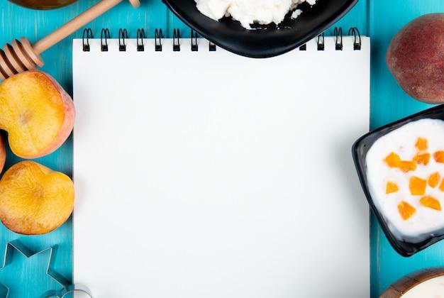 Bovenaanzicht van een schetsboek en verse rijpe perziken kwark yoghurt en cookie cutters gerangschikt op blauw