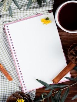 Bovenaanzicht van een schetsboek met een mok thee en verspreide paardebloemen op hout