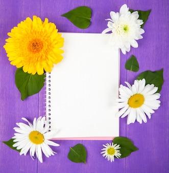 Bovenaanzicht van een schetsboek met madeliefje en gerberabloemen op paarse houten achtergrond