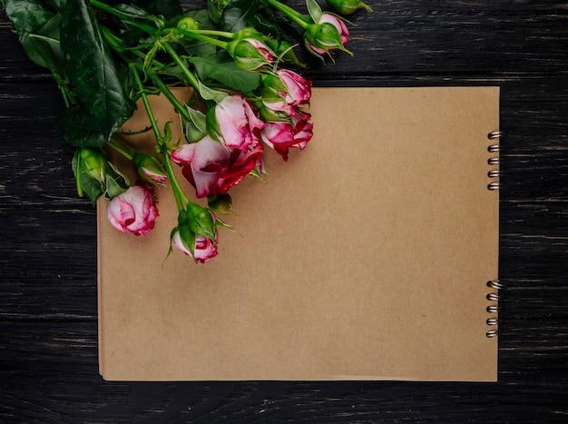 Bovenaanzicht van een schetsboek met roze kleurenrozen met knoppen die op donkere houten achtergrond liggen