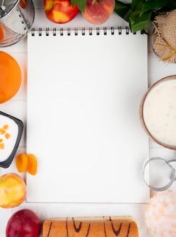 Bovenaanzicht van een schetsboek met verse perziken yoghurt kwark en jam op wit