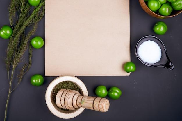 Bovenaanzicht van een schetsboek, zout, gedroogde pepermunt in een vijzel, venkel en zure groene pruimen verspreid over zwarte tafel