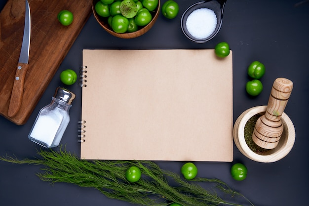 Bovenaanzicht van een schetsboek, zoutvaatje, gedroogde pepermunt in een vijzel en zure groene pruimen in een houten kom op zwarte tafel