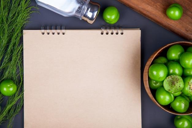 Bovenaanzicht van een schetsboek, zoutvaatje, venkel en zure groene pruimen in een houten kom op zwarte tafel