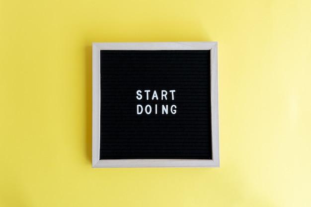 Bovenaanzicht van een schoolbord met een massage op een gele achtergrond